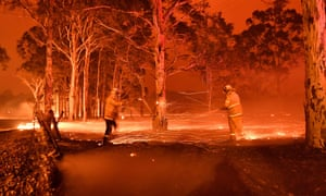 This timed-exposure image shows firefighters hosing down trees as they battle against bushfires around the town of Nowra in the Australian state of New South Wales on December 31, 2019.