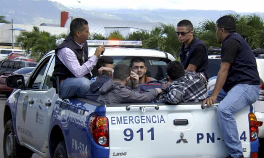 Policemen escort five Syrian men after they were detained at Toncontin international airport in Tegucigalpa, Honduras.