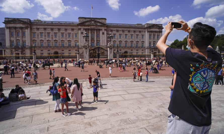 A man takes a picture of Buckingham Palace, in London, Saturday, June 5, 2021