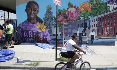 """A boy rides his bicycle Monday, July 29. 2019 after volunteering to paint a mural outside the New Song Community Church in the Sandtown section of Baltimore. In the latest rhetorical shot at lawmakers of color, President Donald Trump over the weekend vilified Rep. Elijah Cummings majority-black Baltimore district as a """"disgusting, rat and rodent infested mess"""" where """"no human being would want to live."""" (AP Photo/Julio Cortez)"""