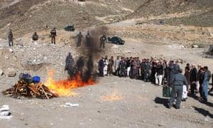 Police officers set seized drugs on fire in Asadabad, Afghanistan