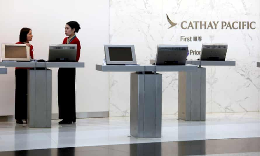 Attendants chat at the first-class counter of Cathay Pacific Airways at Hong Kong airport