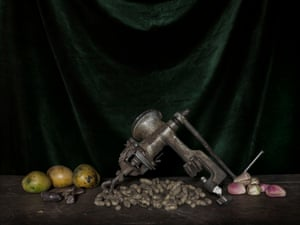 A table in Amina Alhadji's home holds mangoes, groundnuts, kola nuts, a nut grinder and a 'waraga' (talisman)