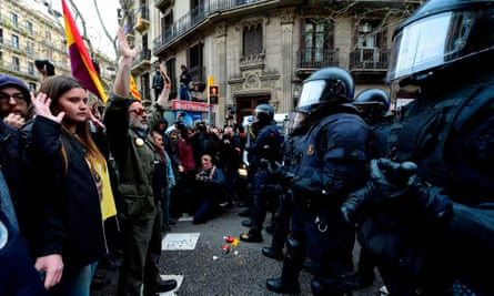 Protesters stand opposite riot police at a demonstration in Barcelona.