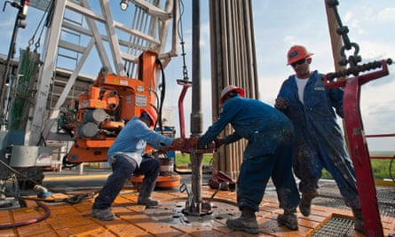 Workers wrestle with a pipe on an oil rig in Texas.