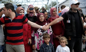 Refugees and migrants wait to welcome Queen Rania of Jordan at the Kara Tepe refugee camp on the island of Lesbos, Greece, on Monday.