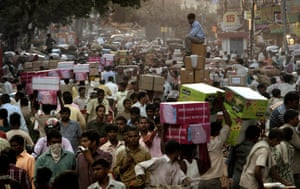 A shopkeeper sits on boxes as he waits for transportation at a busy wholesale market in New Delhi, India.
