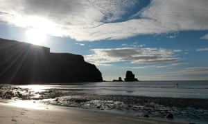 Rebecca Howett wades into the water at Talisker Bay, Skye