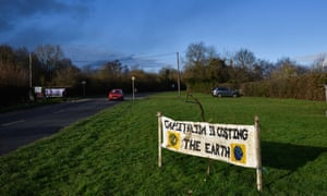 A protest sign which reads 'Capitalism is costing the earth' alongside a road in Harefield, England