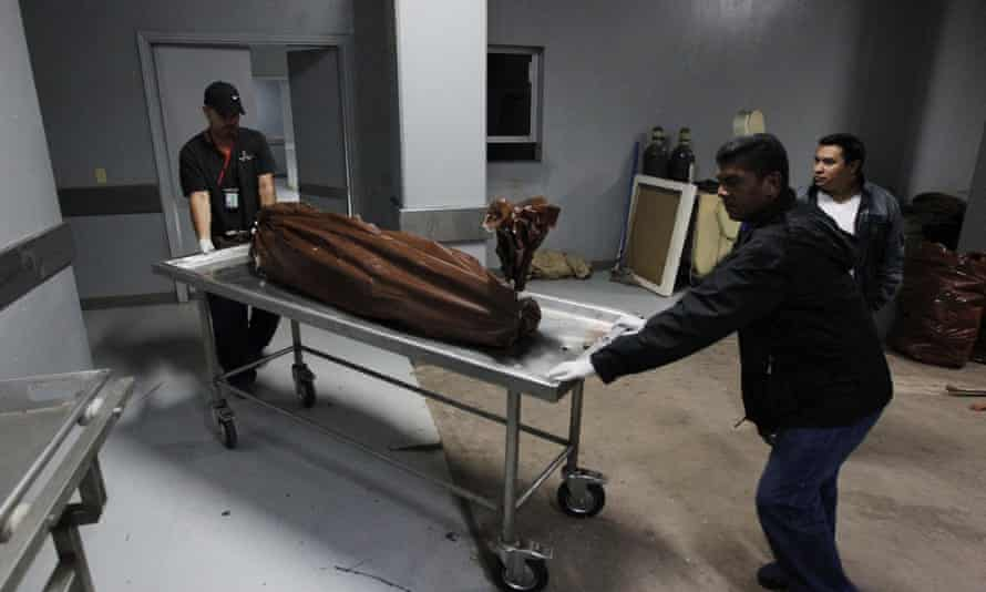 Technicians wheel a stretcher with a body bag, containing the body of a young man who was shot by members of street gang Mara 18 for attempting to steal a motorcycle, at a morgue in Tegucigalpa, Honduras.
