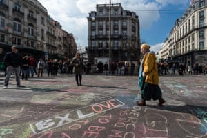 A man walks by solidarity messages written in chalk outside the stock exchange in Brussels