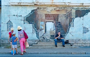 A man is eating his ice-cream while texting in front of a mural in Swanage, Dorset, as mother looks on, explaining the picture to her children