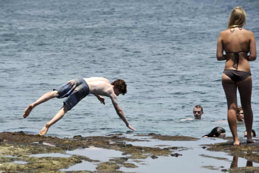 A boy jumps from the rocks at north Bondi in Sydney on Tuesday as a blast of summer heat hit Australia's south-east.