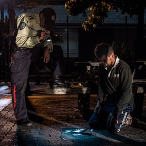 A policeman searches a homeless man suspected of stabbing a person in order to rob him