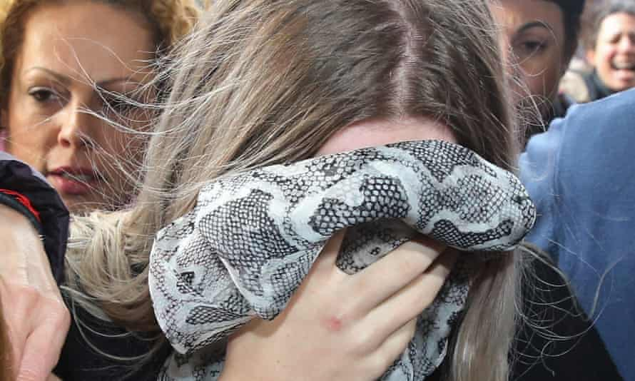 A British woman and alleged victim of a gang-rape covers her face as she arrives at Famagusta district court in Paralimni, Cyprus, on 7 January.