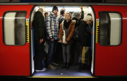 Commuters on a tube at Oxford Street station.
