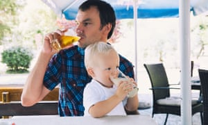 Father drinks beer, child, sitting on his lap, drinks juice in a beach bar.