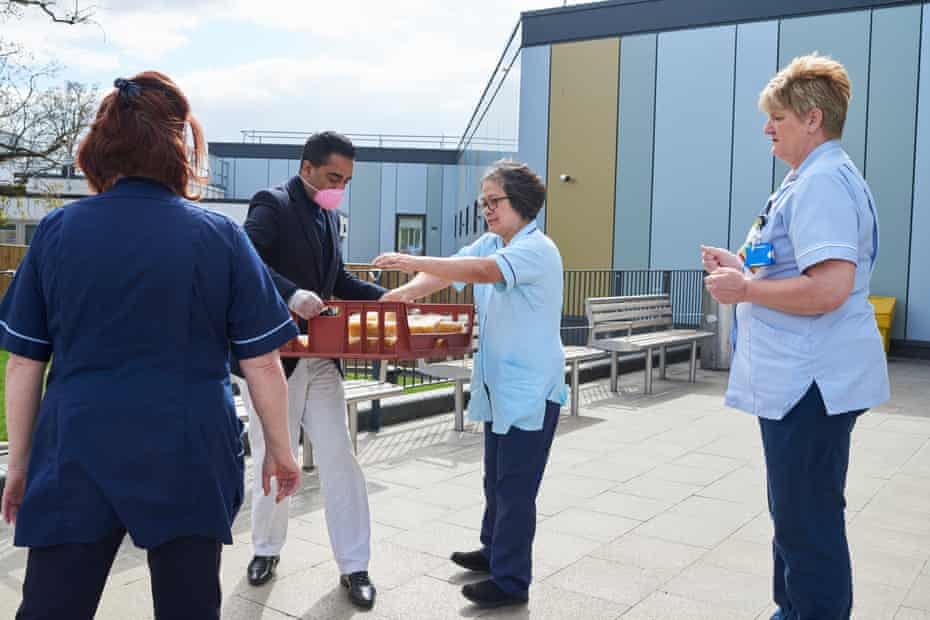 A man in a mask handing out lunches to nurses in uniform.