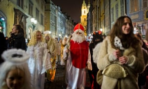 A man dressed as St. Nicholas, accompanied by angels and devils, walks through city centre on December 5, 2014 in Prague, Czech Republic.