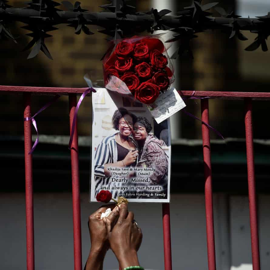 A woman attaches a red rose to a poster of a person missing afte the Grenfell Tower fire in north Kensington