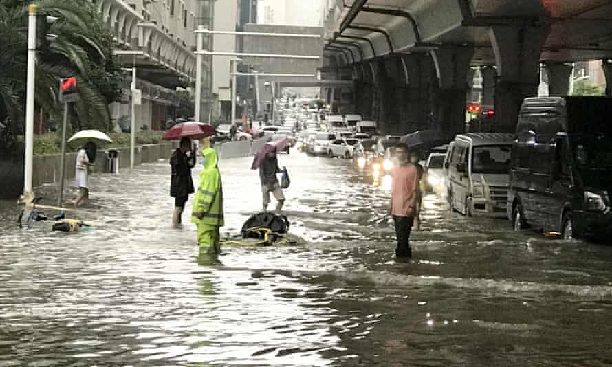 Vehicles and pedestrians on a flooded road in Wuhan