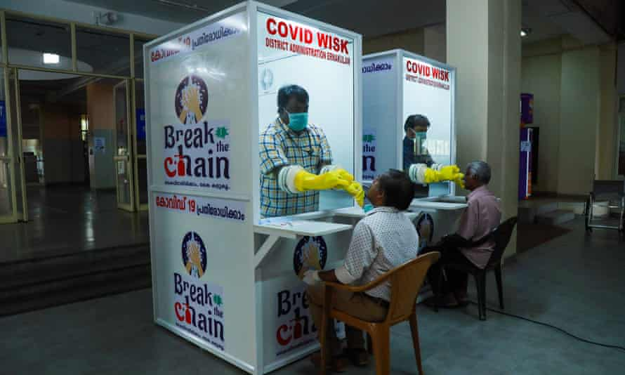 Medical staff test people for coronavirus in kiosks at Ernakulam medical college in Kerala.