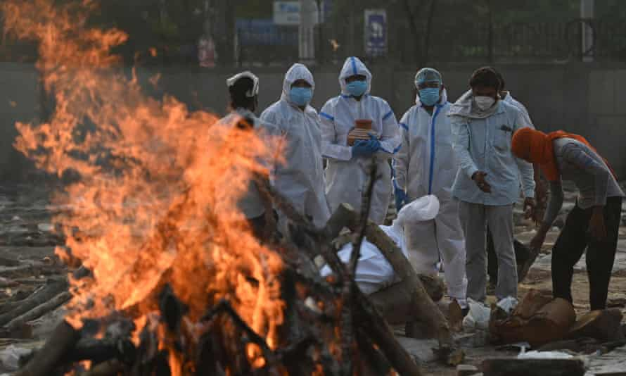 Relatives wearing personal protective equipment (PPE) perform rituals during the cremation of a loved one at a crematorium in New Delhi.