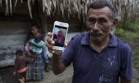 Domingo Caal, 61, holds a smartphone displaying a photo of his granddaughter Jakelin.