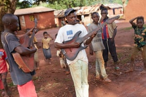 Troubadors with their guitars wander the streets of Boboua village, Central African Republic. 2017