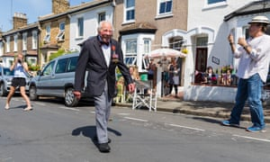 Royal Navy veteran, Charles Medhurst, 95, walks along his street for a victory parade as his neighbours cheer and clap in Greenwich, London.