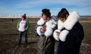 Young villagers check their cell phones.