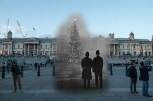 Two police officers look at a 64ft Christmas tree in Trafalgar Square on 1 December 1 1948. Tourists walk through the area on 23 November 2017