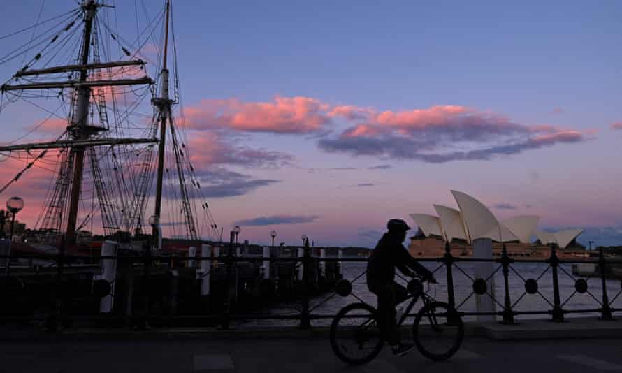 A lone person rides a bicycle past the Sydney Opera House in Sydney at sunset