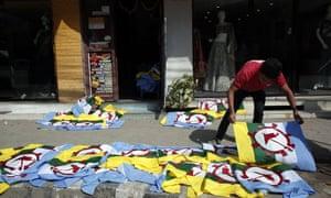 A man dries screen-printed flags of the Rastriya Prajatantra party in Kathmandu