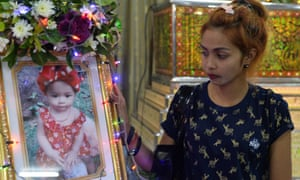 Jiranuch Trirat, mother of the 11-month-old who was killed by her father, stands next to a picture of her daughter at a temple in Phuket.