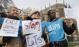 Protestors against disability benefit cuts hold banners near parliament in London, March, 2017. (AP Photo/Kirsty Wigglesworth)