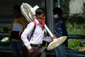 A migrant worker carrying a fan walks along a road as he leaves India's capital for his home