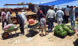 Libyans shop for vegetables at an open-air market in Tripoli.