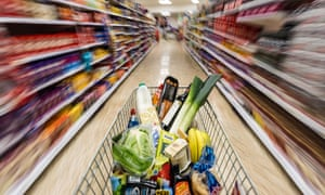 A shopping trolley with groceries is pushed around a supermarket in London, UK.
