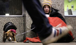 Dawn, a homeless woman from north Wales, sits huddled under a sleeping bag next to her dog in London