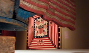 """a patriotic quilt is framed by a flag trailing """"Uncle Sam on a Bicycle Whirligig"""" at the exhibit """"American Made: Treasures from the American Folk Art Museum"""" at the Crystal Bridges Museum of American Art in Bentonville"""