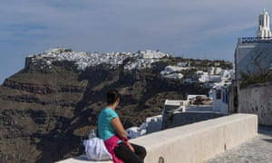 Female holidaymaker gazes at the town of Fira on the Greek island of Santorini in the Aegean Sea.