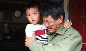 Le Minh Tuan, the father of 30-year-old Le Van Ha, who is feared to be among the 39 people found dead in a lorry in Essex, holds Ha's five-year-old son.