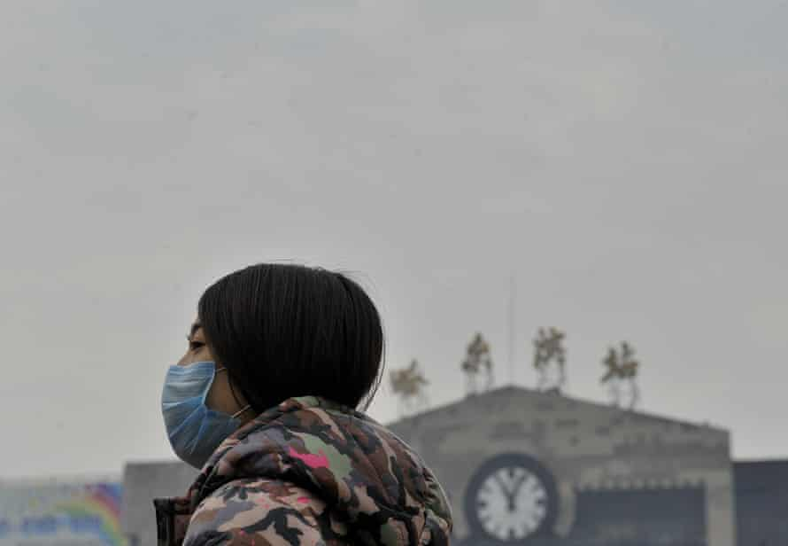 A woman wears a mask in front of Harbin railway station in China