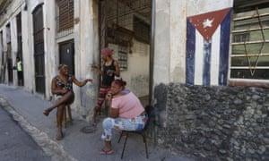 Women chat on the sidewalk in Havana