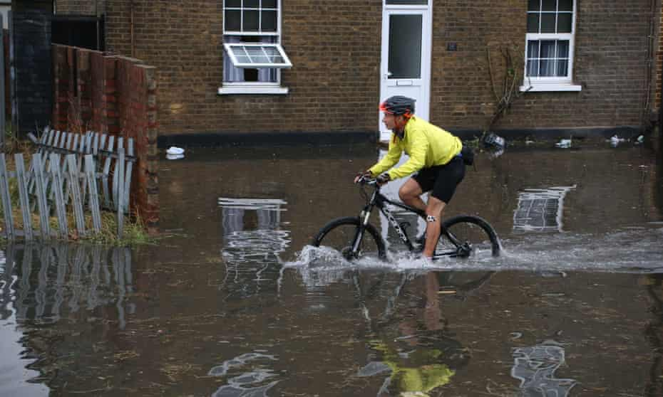 A cyclist makes his way through floodwaters in north-east London on 25 July 2021.