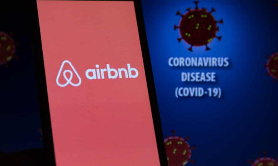 Airbnb logo and Covid-19 is displayed on a smartphone