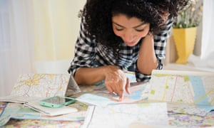 Woman planning a road trip with maps