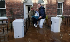 Margaret McCraken, 79, is helped from her home in Broad Street in Carlisle through the floods by members of the armed forces who have been called in to help evacuate people who wish to move