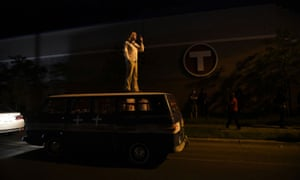 A medic supervises demonstrations from the roof of a makeshift medic van outside the fifth police precinct in Minneapolis